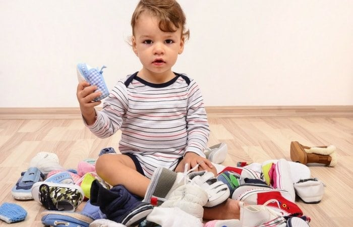 toddler in a pile of shoes let it go