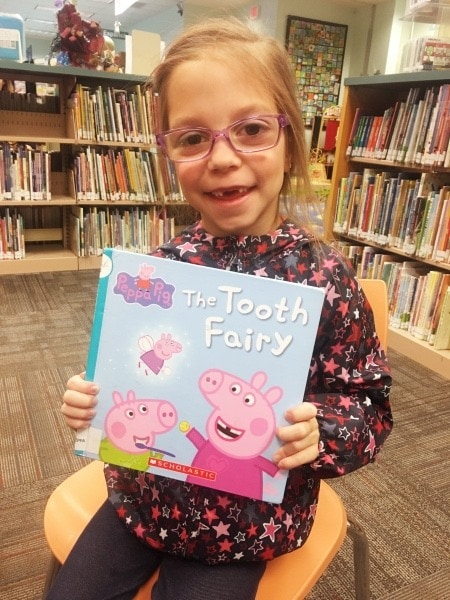 girl holding book tooth fairy