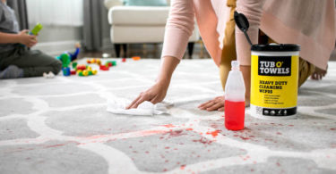 woman cleaning stain on rug after school messes