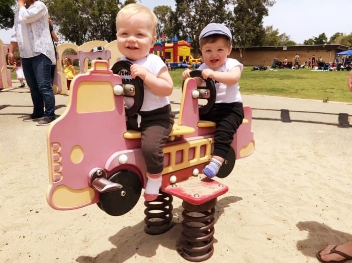 twins on a bouncy playground firetruck ride twin parents