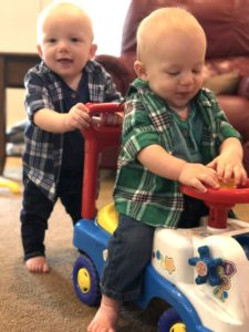 twin boy toddlers playing with ride on car stay-at-home parents of twins