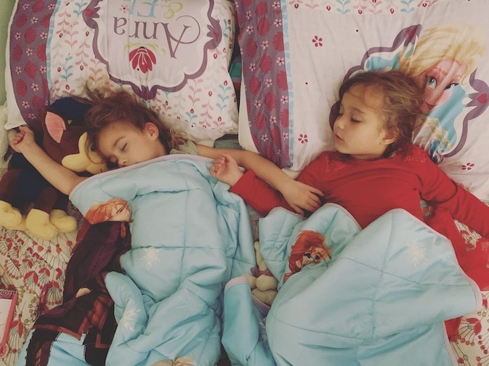 twin girls asleep in bed during a pandemic