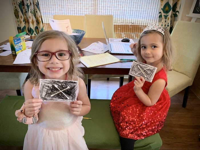 twin girls holding up an art project during a pandemic