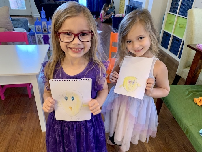 twin girls holding up drawings during a pandemic