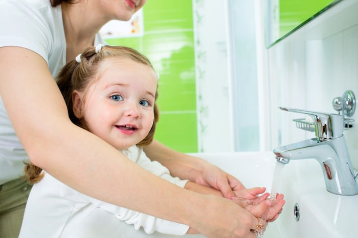 girl washing her hands potty training twins